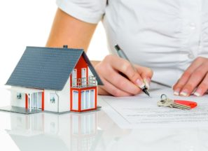 a woman signs a purchase contract for a home with a real estate agent.